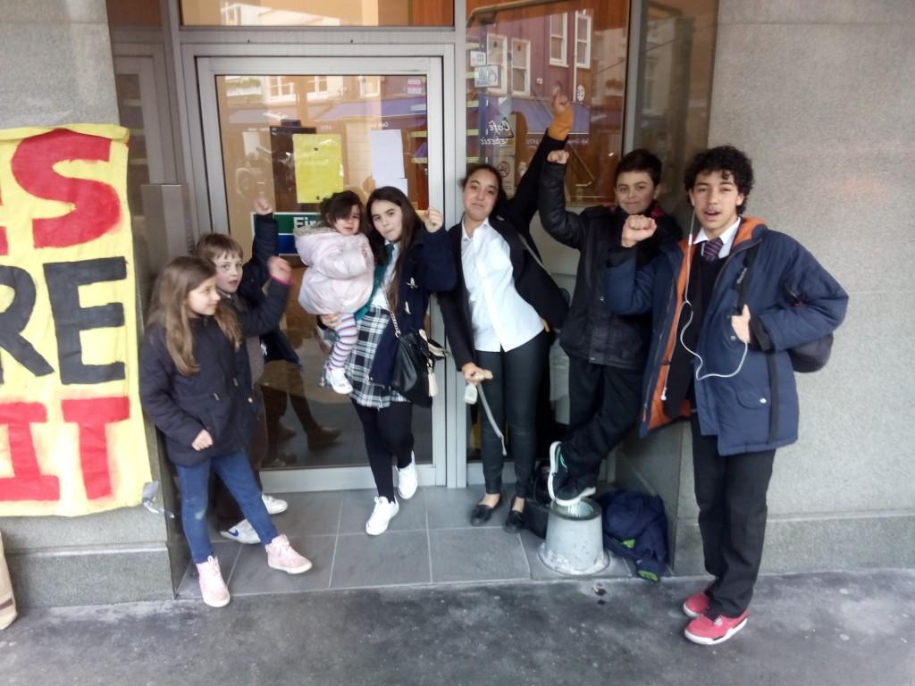 """Sweets wayi diákok. A mellettük lévő molinó felirata: """"people before profit""""."""